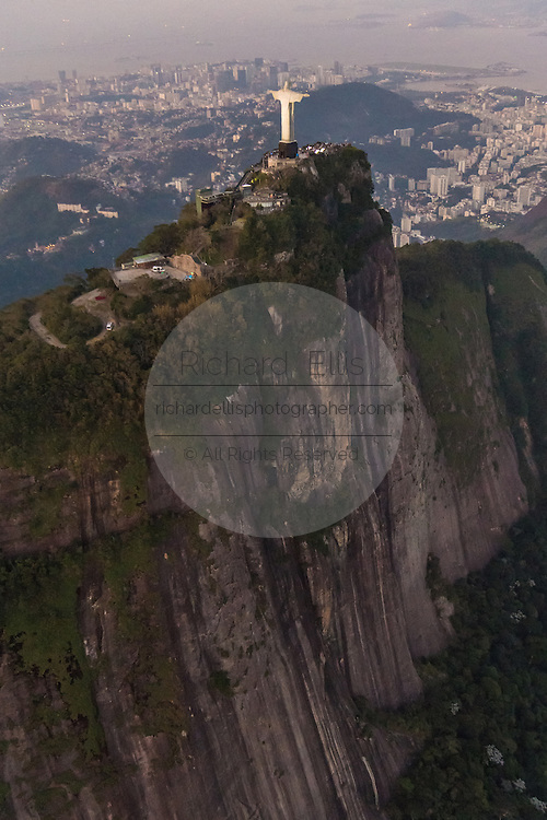 Christ the Redeemer statue on Corcovado Mountain looking toward Centro business district at sunset in Rio de Janeiro, Brazil.