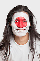 Portrait of happy young man with long hair and Japanese flag painted on face against white background