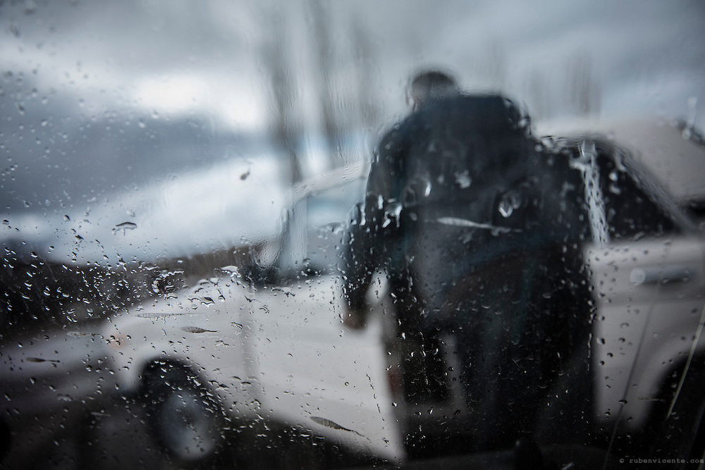 A man at Zovasar entering his Lada car in the rain. Armenia