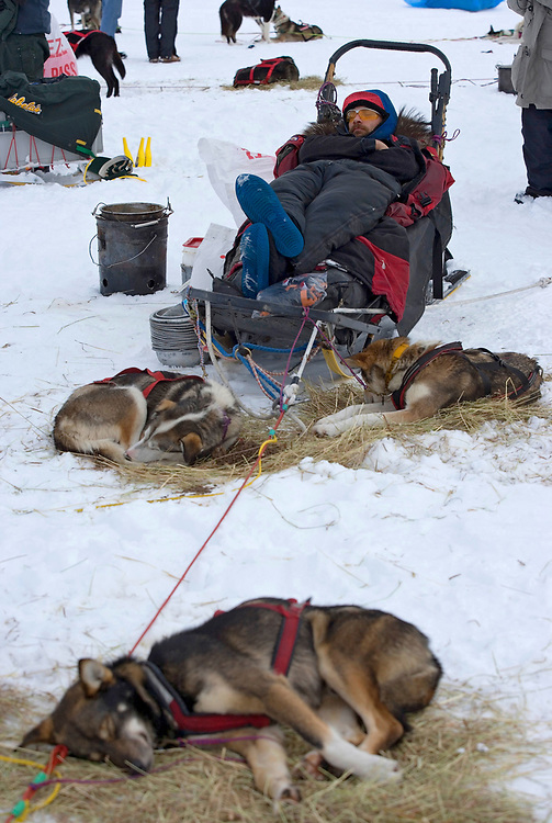 USA, Alaska, Puntilla Lake, Musher Lance Mackey sleeps on sled by his team at Rainy Pass checkpoint during 2005 Iditarod sled dog race
