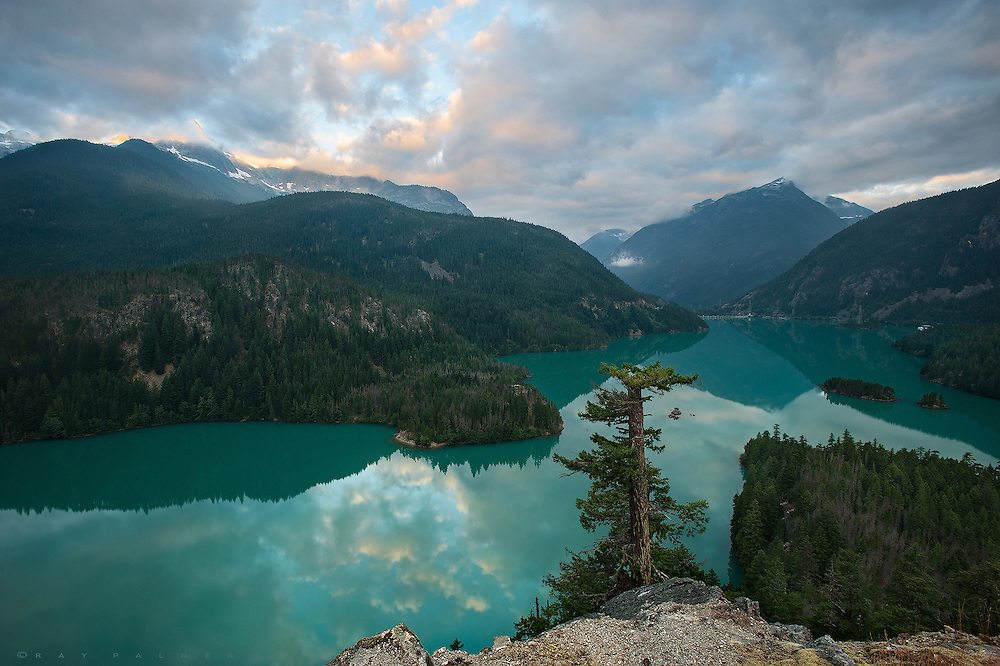Diablo Lake, North Cascades, Washington.  I brought my demons to paradise.   At the time, months of constant sciatic pain were a cloud around me, physically and mentally.  If there was devil, he had gotten into my leg and made every day an agony.  Part of me just wanted to lie in a fetal position where nothing hurt.  I tried to exert the nerve into remission, but the more I pushed it, the worse it got.  But I am a stubborn man.  I felt I could cure myself if I could just make my body stronger, stretch it out, exorcise the pain.  Despite everyone's criticisms that I was aggravating things more, I ultimately refused to give up a planned trip, and came to this slice of heaven, to climb mountains.  Every day I hurt at the start and end, but not so much as I pushed myself through the hikes.  Since I began coming out here, the North Cascades had always seemed mystical to me.  Darkly forested and impossibly steep, the trails are often lost under snow pack late into August, and yet they are a pure pleasure to hike, and a feast for the eyes.  This day's slog was over, and, camp made, I went looking for a sunset.  I found it above the water-can't-really-be-that-color-i-don't-believe-it of Diablo Lake. But it's real.  Maybe the devil in me decided to go play in paradise while I was so distracted.  Maybe it was more a departure than a cure.  Within a couple of weeks of returning home, my nerve pain was gone, the cloud had lifted like the one I saw on this night, revealing the shine of hope.  I left some pain in these mountains.  But, there is always more to be found.  I remain stubborn.  Maybe I can find another devil's paradise.