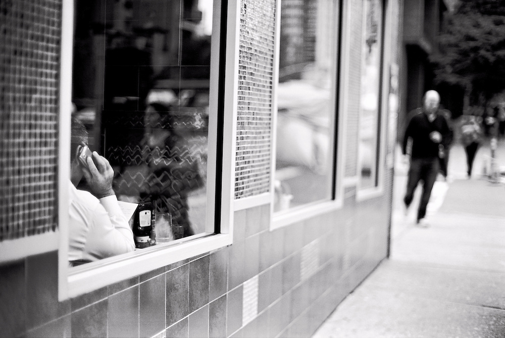 Man on cell phone seen through diner window