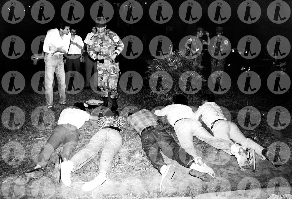 Un miembro de la Policia Nacional toma datos a estudiantes de la Universidad de El Salvador que fueron capturados a la salida de la universidad de El Salvador acusandoles de pertenecer a los comandos urbanos del Frente Farabundo Marti FMLN.(IL Photo).