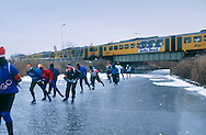 Nederland, Molkwerum, 19970104..De Elfstedentocht in januari 1997 in Friesland..Schaatsers rijden door de polders. Trein komt voorbij.  6000 schaatsers en meer dan een miljoen toeschouwers..The Elfstedentocht is a speed skating competition and leisure skating tour in the province of Friesland in the Netherlands..Skaters driving towards the setting sun.6.000 skaters and over a million spectators were present. The route takes the skaters through eleven cities in Frisia, in the North of Holland. 200 kilometre race along the frozen canals of Friesland..