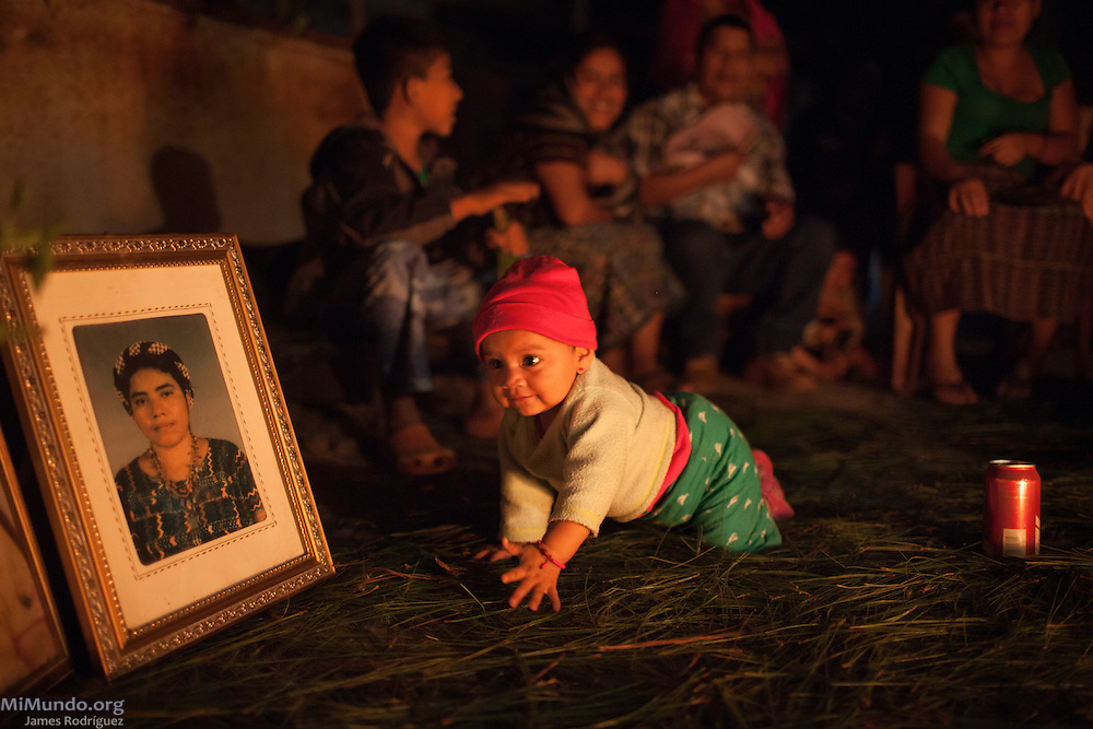 A baby crawls near the photos of family members killed during the Rio Negro massacres as friends and family of the Chen family gather for a Mayan Ceremony at their home in Pacux the evening before the Guatemalan government is to begin paying reparations to  hundreds of families from 33 former communities submerged during the construction of the Chixoy hydro-electric dam and subsequent flooding of the Chixoy River basin in the early 1980's. The community of Pacux, in the outskirts of Rabinal, is where the former Achi Mayan residents of Rio Negro were resettled after the destruction and flooding of their village. Carlos Chen, Rio Negro survivor, has led the search for reparations via his organization COCAHICH (Coordinating Committee of Communities Affected by the Construction of the Chixoy Dam) since 2004. Pacux, Rabinal, Baja Verapaz, Guatemala. October 14, 2015.