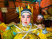 17 FEBRUARY 2016 - BANGKOK, THAILAND:  A Chinese opera performer gets help getting into her costume backstage before a performance in Bangkok. The small troupe travels from Chinese shrine to Chinese shrine performing for a few nights before going to another shrine. They spend about half the year touring in Thailand and the other half of the year touring in Malaysia. Members of the troupe are paid about 5,000 Thai Baht per month (about $140 US). Chinese opera was once very popular in Thailand, where it is called Ngiew. It is usually performed in the Teochew language. Millions of Chinese emigrated to Thailand (then Siam) in the 18th and 19th centuries and brought their culture with them. Recently the popularity of ngiew has faded as people turn to performances of opera on DVD or movies. There are still as many 30 Chinese opera troupes left in Bangkok and its environs. They are especially busy during Chinese New Year and Chinese holiday when they travel from Chinese temple to Chinese temple performing on stages they put up in streets near the temple, sometimes sleeping on hammocks they sling under their stage. Most of the Chinese operas from Bangkok travel to Malaysia for Ghost Month, leaving just a few to perform in Bangkok.    PHOTO BY JACK KURTZ