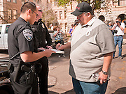 22 FEBRUARY 2011 - PHOENIX, AZ:  Capitol Police cite Carlos Galindo at the State Capitol in Phoenix Tuesday. Hundreds of people including supporters of immigrants' rights, supporters of border defense, motorcycle riders and members of the Tea Party, converged on the capitol to express their views on bills. Galindo and several others allegedly disrupted a committee hearing Tuesday.     PHOTO BY JACK KURTZ