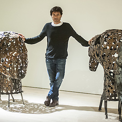 London, UK - 2 September 2014: Artist Xavier Mascaró poses next to an iron portrait of a young woman from the Eleonora series reminiscent of the profiles on ancient coins. Xavier Mascaró's first UK solo exhibition will run from 3 September until 5 October at Saatchi Gallery.