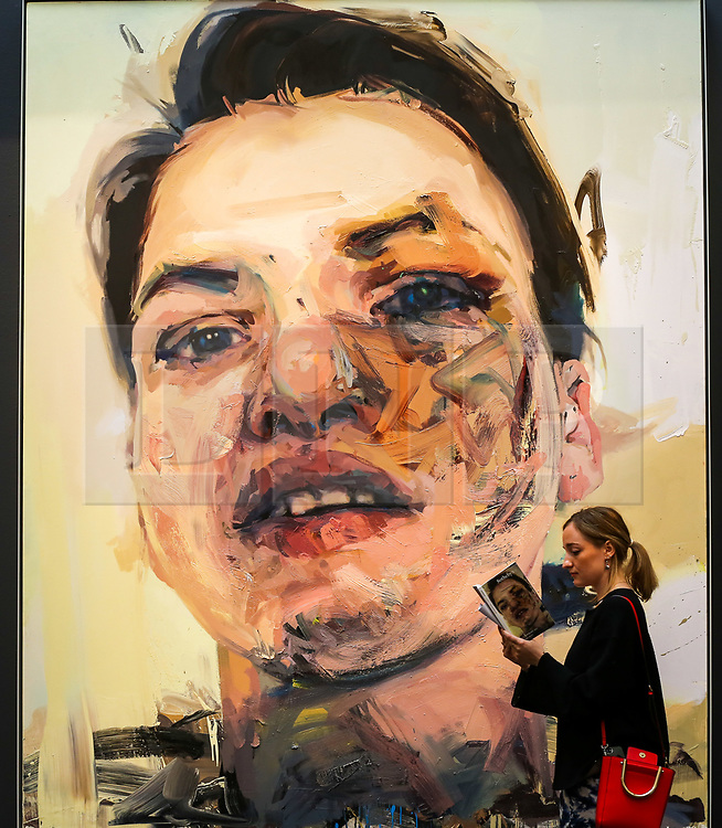 """© Licensed to London News Pictures. 21/06/2019. London, UK. A woman views the brochure in front of Jenny Saville's """"Shadow Head"""", 2007-13 (Est £3m- £5m) at the preview of Summer Contemporary Art Auctions at Sotheby's George Street, London. Photo credit: Dinendra Haria/LNP"""