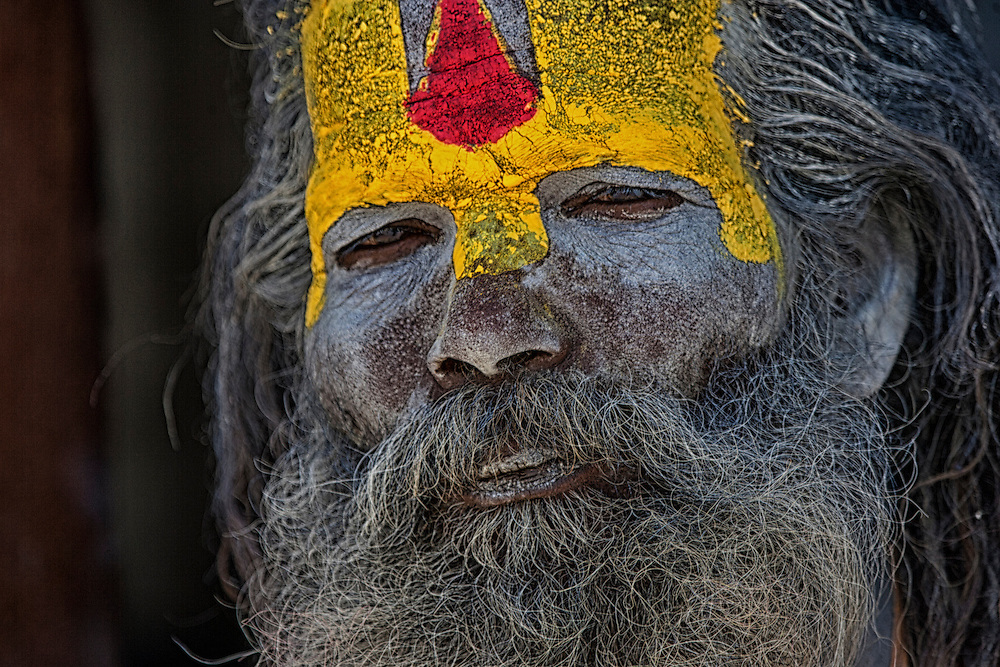 A Katmandu Sadhu, or holy man, looks on from a temple.  In Hinduism, a sadhu is an ascetic wandering monk.  According to, Wikipdeia,  the sadhu is dedicated to achieving liberation and the final stage of life through meditation and contemplation of brahman.  Sadhus have left behind all material and sexual attachments.  There are 4 to 5 million living in India today.