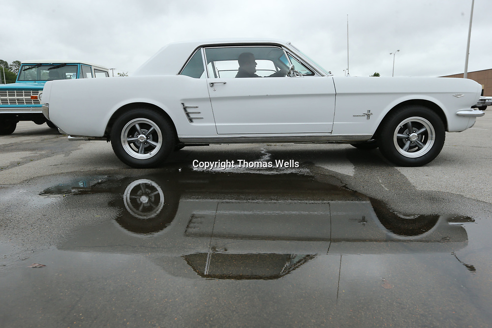 A 1960's era Ford Mustang avoinds a puddle of water early Friday mornign as this yer's Blue Suede Cruise gets underway.