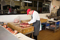 Male butcher slicing beefsteak in store