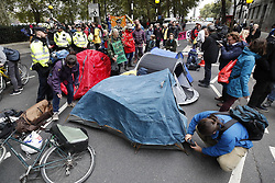 © Licensed to London News Pictures. 07/10/2019. London, UK. Extinction Rebellion protestors erect tents Millbank near Parliament in central London . Activists will converge on Westminster blockading roads in the area for at least two weeks calling on government departments to 'Tell the Truth' about what they are doing to tackle the Emergency. Photo credit: Peter Macdiarmid/LNP