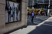 Man walks past a stylish clothing shop for businessmen on a poster in the City of London.