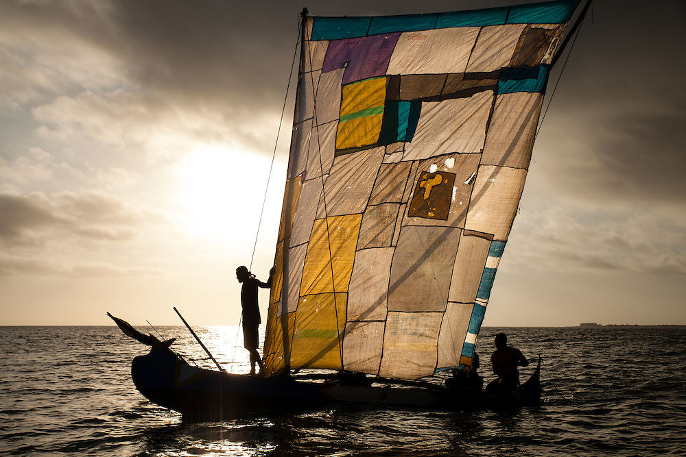 As the sun rises, traditional Vezo fishermen sail from the sand cay they live on far out into the Mozambique channel.  As long as the winds are good, the fishermen's daily routine is one of rising at 3 am so that they can catch the favourable winds before dawn; they sail 20 to 60 km further out into the channel and spend the day free diving and checking their shark nets; then sail back in the afternoon.