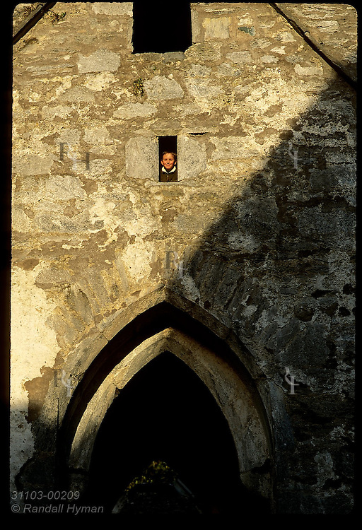 Boy peers from window opening on upper floor of Muckross Abbey, built by Franciscan friars in 1400s; Killarney Natl Park, Ireland.
