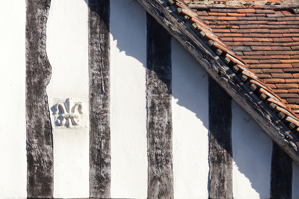 Pargetted fleur de lis symbol on the 16th century timber studded gable of a medieval house in Lavenham, Suffolk, UK.