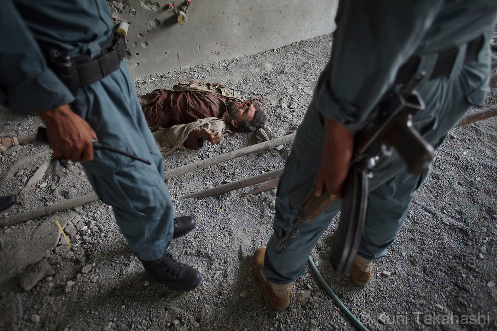 Afghan policemen stand near the body of one of the insurgents laying down in the building near the U.S Embassy in Kabul, Afghanistan on Sep 14, 2011 after he was killed during an operation by Afghan and NATO coalition forces. Terrorists attacked multiple locations including U.S. Embassy and a nearby NATO base in Kabul..(Photo by Kuni Takahashi) .