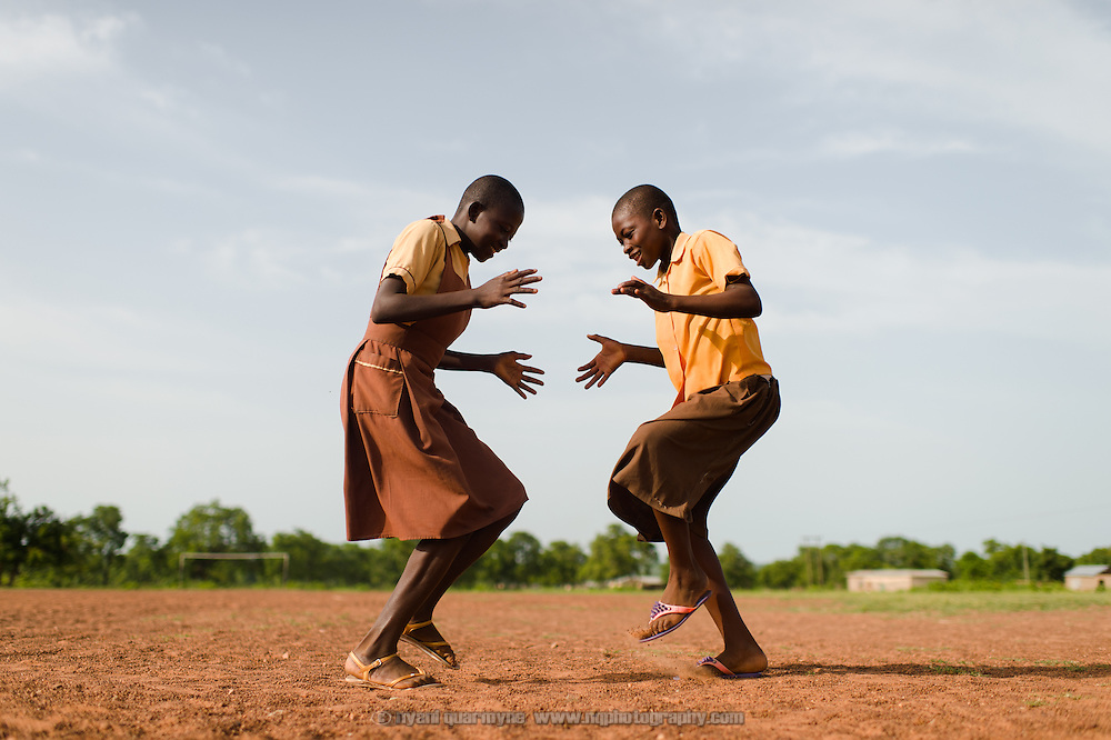 Hafisa (left) and Mansura playing ampeh, a traditional game similar to rock-paper-scissors, on the football pitch at their school in the Upper West region of Ghana on 28 May 2014.