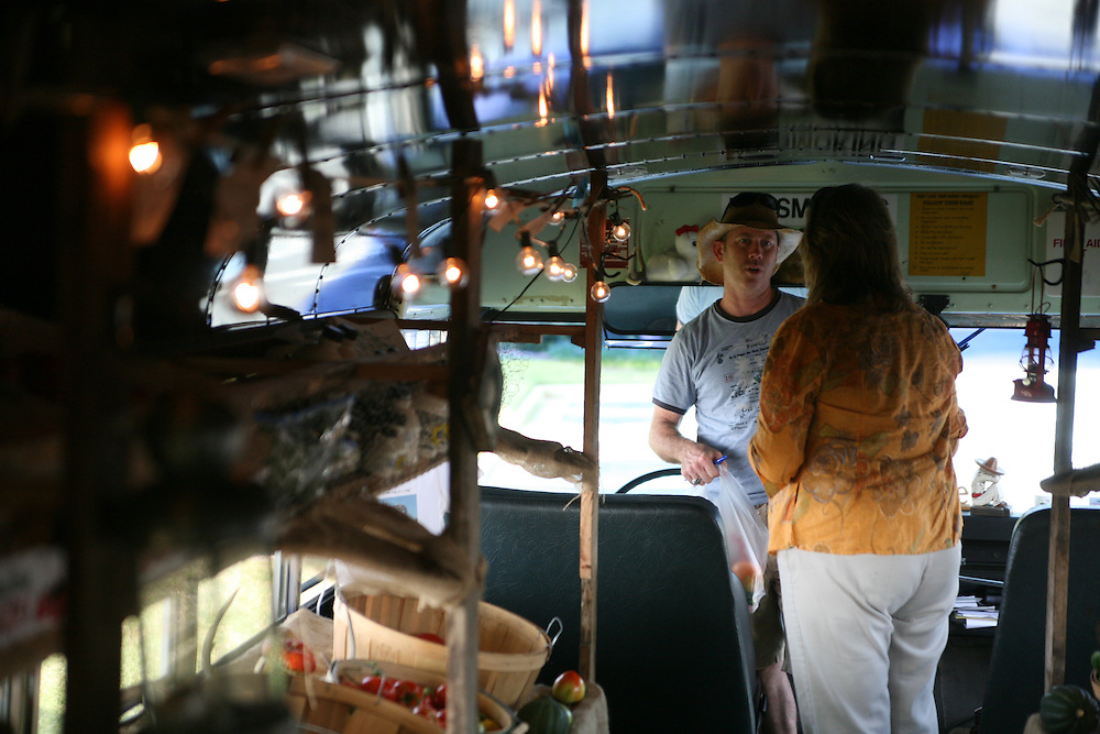 A woman purchases produce from the Farm to Family Market--a market in a converted school bus. Photographed for the Virginia Sustainable Agriculture Documentary Project.