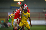 Fleetwood Town Defender Conor McLaughlin (2) meets the ball ahead of Fleetwood Town Forward Bobby Grant (11)  and AFC Wimbledon forward Tom Elliott (9)  during the EFL Sky Bet League 1 match between Fleetwood Town and AFC Wimbledon at the Highbury Stadium, Fleetwood, England on 18 March 2017. Photo by Simon Davies.
