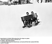 Hugo Spowers & Hubie Gibbs going down the slope on a piano during the Dangerous Sports Club Ski race. St. Moritz. 1983.<br />