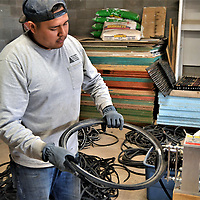 Cornfields Chapter maintenance worker Vernell Joe slices up a cleaned tire side into long ribbons of rubber, which are then cut into various sizes before holes are punched into them so they can be woven into door mats.