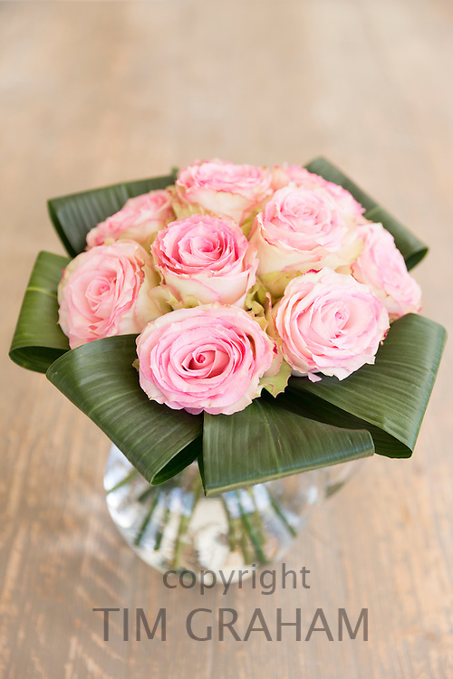Vase of flowers - Lace-edged  pastel pink roses in an elegant bouquet style floral arrangement with banana leaves in glass jug