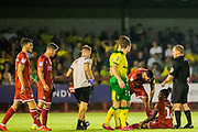 John Busby (Referee) with injured David Sesay (Crawley Town) as assistance arrives to assess him during the EFL Cup match between Crawley Town and Norwich City at The People's Pension Stadium, Crawley, England on 27 August 2019.