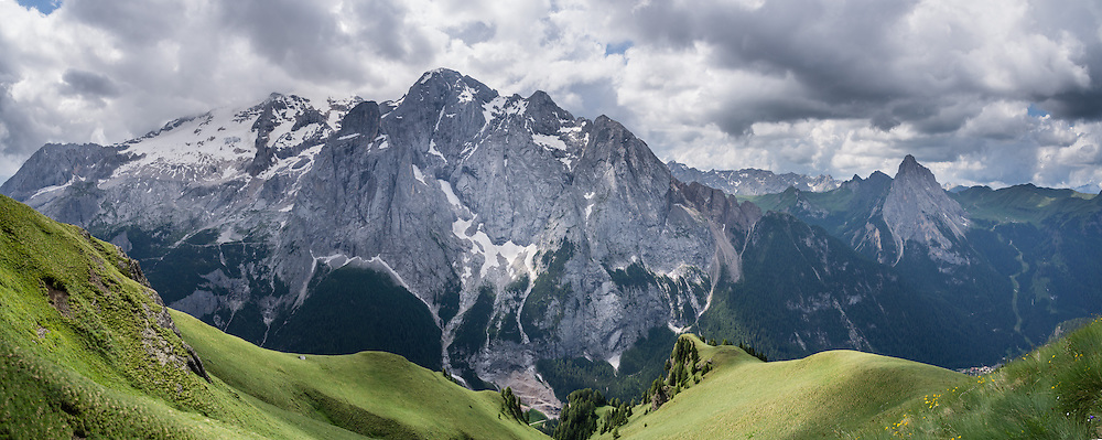 Starting from Pordoi Pass in Italy, we highly recommend hiking the Bindelweg/Viel del Pan trail for a majestic perspective on the Queen of the Dolomites, glacier-clad Marmolada (3343 meters / 10,968 feet). Take state highway 48 (Grand Strader delle Dolomiti) to Pordoi Pass and hike up the Padon chain, a ridge of volcanic origin carpeted with lush green pasture and wildflowers. Hike an easy 5 miles with 1000 feet gain round trip to Rifugio Viel del Pan; or walk one way 4 miles to the lift at Porta Vescovo down to Arabba village, where an SAD bus can return you to Pordoi Pass during lift hours; or walk 3 hours to Lago di Fedaia and bus back. Pordoi Pass (or Pordoijoch, 2239 meters/7346 feet) is the highest surfaced road traversing a pass in the Dolomites. The Dolomites are part of the Southern Limestone Alps, Europe. UNESCO honored the Dolomites as a natural World Heritage Site in 2009. This panorama was stitched from 3 overlapping photos.