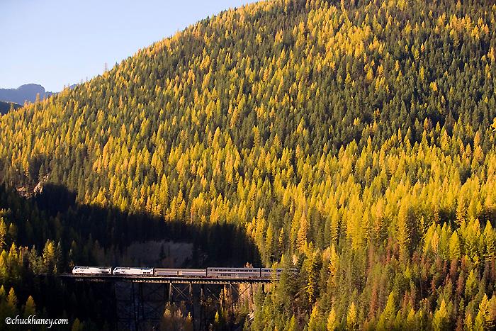 Amtrak passenger train crosses trestle near the Goat Lick in Glacier National Park in Montana