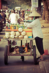 Coconut seller on a crowded street in  in  Ho Chi Minh city (HCMC), Vietnam, Asia. Her kid takes a nap in a special compartment arranged in the trolley.