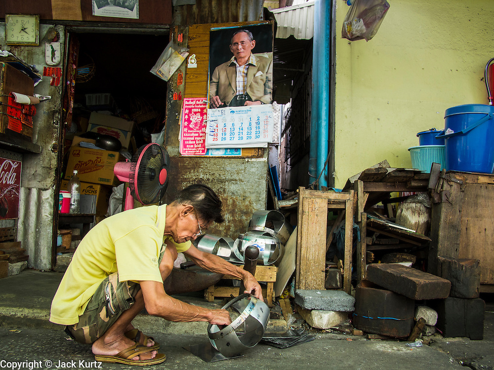 """19 AUGUST 2013 - BANGKOK, THAILAND:     A man makes monks' bowls, called """"bat"""" (pronounced with a long """"a"""" as in baat) under of a portrait of Bhumibol Adulyadej, the King of Thailand, on Soi Baan Bat in Bangkok. The bowls are made from eight separate pieces of metal said to represent the Buddha's Eightfold Path. The Monk's Bowl Village on Soi Ban Baat in Bangkok is the only surviving one of what were originally three artisan's communities established by Thai King Rama I for the purpose of handcrafting """"baat"""" the ceremonial bowls used by monks as they collect their morning alms. Most monks now use cheaper factory made bowls and the old tradition is dying out. Only six or seven families on Soi Ban Baat still make the bowls by hand. Most of the bowls are now sold to tourists who find their way to hidden alleys in old Bangkok. The small family workshops are only a part of the """"Monk's Bowl Village."""" It is also a thriving residential community of narrow alleyways and sidewalks.  PHOTO BY JACK KURTZ"""