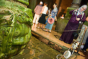 08 AUGUST 2007 -- ISTANBUL, TURKEY: Tourists look at and photograph the Medusa heads inside the Basilica Cistern in Istanbul, Turkey. The Cistern was created by Roman Emperor Justinianus in the 6th Century as the city's water supply. Historians and archeologists aren't sure of the origin of the Medusa heads. Istanbul, a city of about 14 million people, and the largest city in Turkey, straddles the Bosphorus Straits between Europe and Asia. It is one of the oldest cities in the world. It was once the center of the Eastern Roman Empire and was called Constantinople, named after the Roman Emperor Constantine. In 1453, Mehmet the Conqueror, Sultan of the Ottoman Empire, captured the city and made it the center of the Ottoman Turkish Empire until World War I. After the war, the Ottoman Empire was dissolved and modern Turkey created. The capitol was moved to Ankara but Istanbul (formerly Constantinople) has remained the largest, most diverse city in Turkey.    Photo by Jack Kurtz