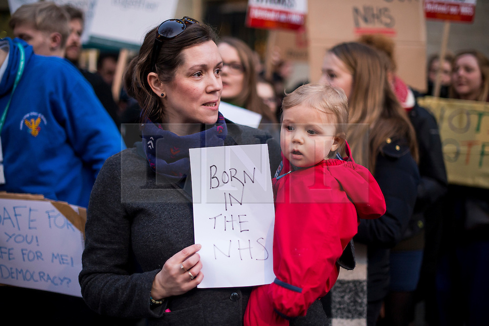 © Licensed to London News Pictures. 11/02/2016. London, UK. A mother and her young daughter hold up a sign as Junior Doctors and supporters protest outside the Department of Health in Westminster London following Jeremy Hunt's announcement to Parliament that he will force through a new junior doctors contract against their will. Photo credit: Ben Cawthra/LNP