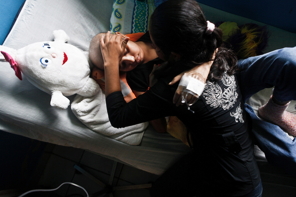 In this photo taken on Friday, Aug. 26, 2011. A leukemia patient Maria Jose Martinez, fourteen  years old embraces with her twin sister Maria Mercedes  at her hospital room 'La Mascota' Managua, Nicaragua. Maria Jose was admitted for her Treatment at La Mascota Hospital in May. 10 of 2011 until August. 29 of 2011, during that period she stayed one month at the intensive care unit. The Association of Parents of children with leukemia and Cancer in Nicaragua, Mapanica, have been organizing for their third year the 15 year old celebration of young girls that have been struggling with the cancer and they still are battling to win this fight against some type of cancer and leukemia at the Childrens hospital La Mascota, in Managua, Nicaragua.
