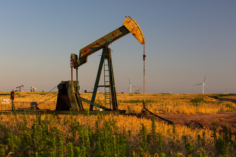Pump jacks and wind turbines in a rural Texas field at dusk.