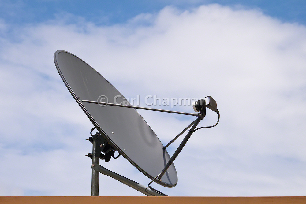 satellite television dish antenna pointing into a cloudy blue sky