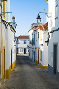 Typical white and yellow houses and lanterns in narrow cobble street in Evora, Portugal