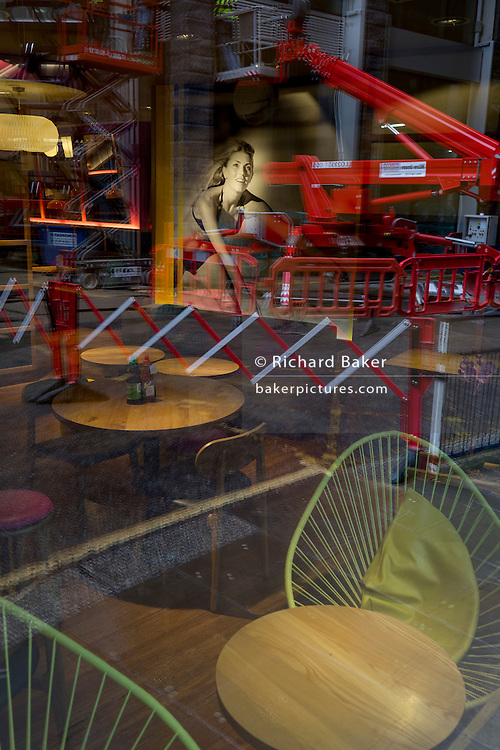 Reflections of construction barriers seen through the window of a city restaurant, on 2nd February 2017, in the City of London, England.