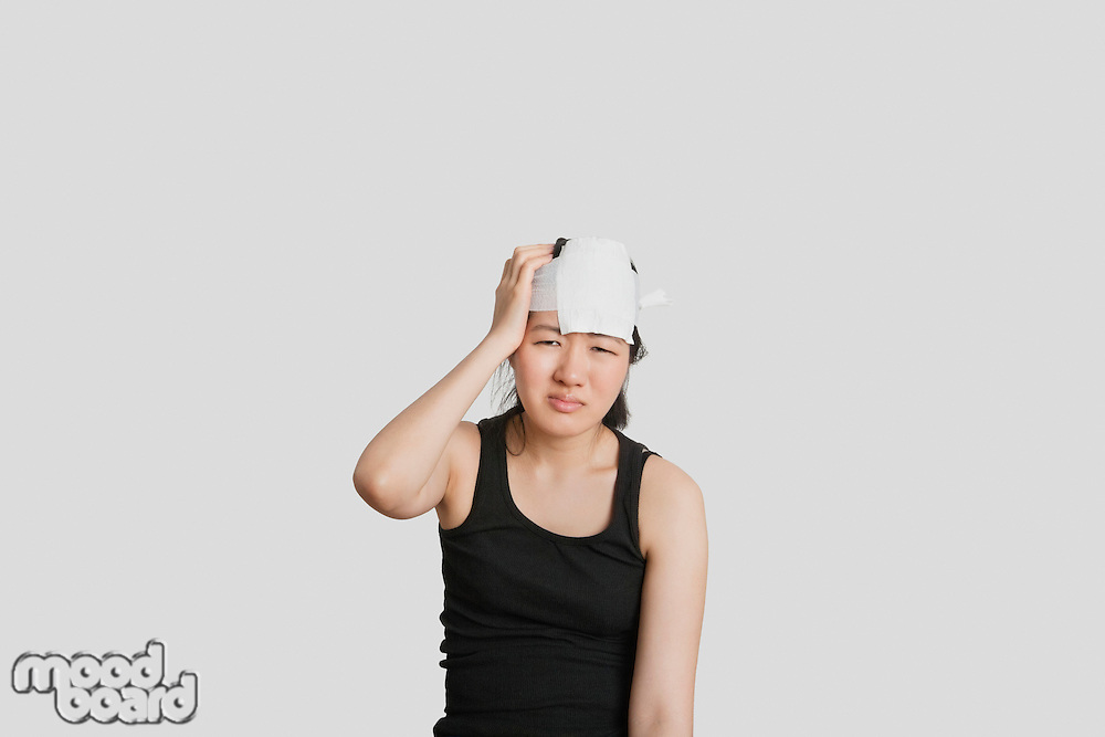 Portrait of a young female in pain with serious head injury