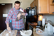 "Jason Holling prepares formula to feed Abby, one week old, before her first doctors visit on September 2, 2014 at their hotel in Illinois. ""Its worth some of the sleepless nights,"" Holling said."