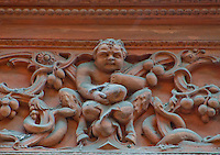 Close-up of a frieze decorating a church in Ticino, Switzerland featuring a greedy hoofed imp surrounded by snakes.