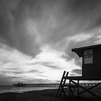 Black and white photo of Lifeguard Tower B and Balboa Pier in Newport Beach California. Newport Beach is a popular coastal beach city along the Pacific Ocean in Orange County Southern California. Copyright ⓒ 2017 Paul Velgos with All Rights Reserved.