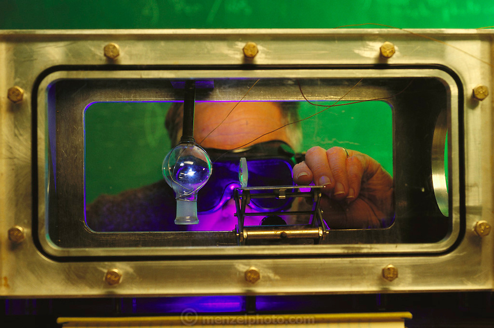 Studying the creation of life. A scientist adjusts equipment during a re-run of the Miller-Urey experiment into the origin of life. A flask containing a mixture of water, hydrogen, methane and ammonia has an electric field applied across it. A ultra-violet laser is used to illuminate the mixture and to stimulate an electrical discharge in the mixture. This experiment, devised first by Stanley Miller and Harold Urey in 1952, produces a mixture of 'pre-biotic' chemicals such as amino acids. It is suggested that the roots of life on Earth rest in prehistoric, global versions of this process. Photographed at the NASA Ames Research Center, California. MODEL RELEASED 1992.