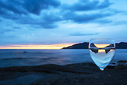 A glass at the shoreline, with sunset and reflection | Et glass i fjæra, med solnedgang og refleksjon.