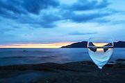 A glass at the shoreline, with sunset and reflection | Et glass i fjæra, med solnedgang og refleksjon.