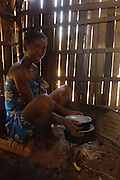 Sakalava woman wearing traditional braided and knotted hair style preparing rice over charcoal fire in her home. The ancestors of this tribe are from mainland Africa. The Sakalavas live along the west coast of Madagascar and are mainly cattle herders.<br />