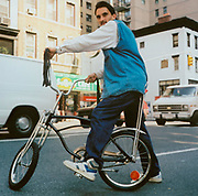 Man on his Schwinn bike with tassles hanging from handle bars, USA