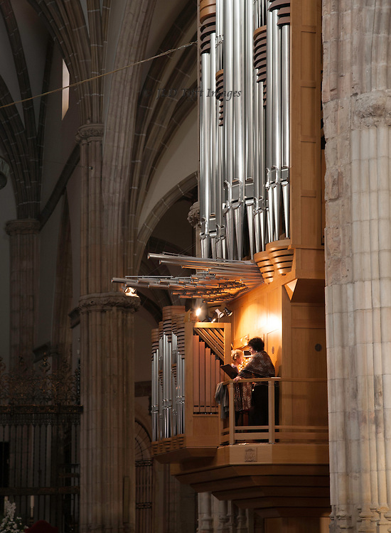 Alcala de Henares cathedral interior showing organ, player, and singer, rehearsing.